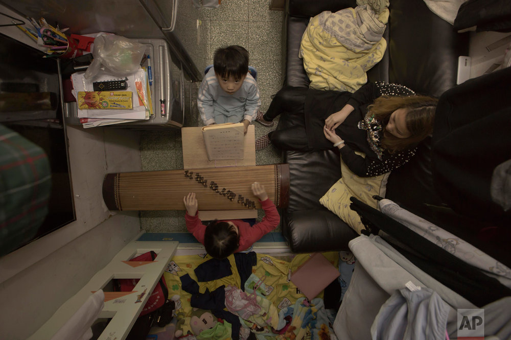 In this Friday, March 17, 2017 photo, Li Suet-wen and her son, 6, and daughter, 8, live in a 120-square foot room crammed with a bunk bed, small couch, fridge, washing machine and small table in an aging walkup in Hong Kong as she pays HK$4,500 ($580) a month in rent and utilities. That's nearly half the HK$10,000 ($1,290) she earns at a bakery decorating cakes. (AP Photo/Kin Cheung)