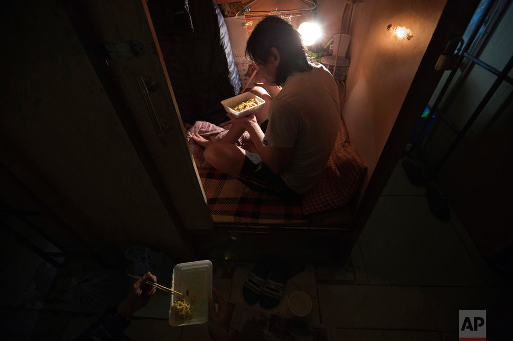 "In this Thursday, March 28, 2017 photo, a resident who only gave his surname Lui, has dinner in his ""coffin home"" in Hong Kong. In wealthy Hong Kong, there's a dark side to a housing boom, with hundreds of thousands of people forced to live in partitioned shoebox apartments, ""coffin homes"" and other ""inadequate housing. (AP Photo/Kin Cheung)"