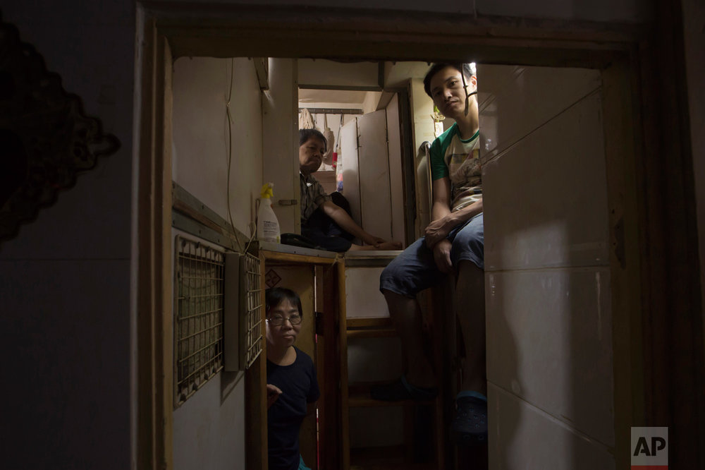 "In this Thursday, May 4, 2017 photo, Hong Kong residents, who only gave their surname, Lam, top left, Wan, top right, and Kitty Au, pose at their ""coffin homes"" in Hong Kong. In wealthy Hong Kong, there's a dark side to a housing boom, with hundreds of thousands of people forced to live in partitioned shoebox apartments, ""coffin homes"" and other ""inadequate housing. (AP Photo/Kin Cheung)"