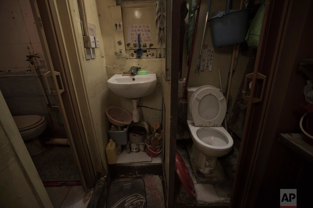 "In this Thursday, March 28, 2017 photo, a set of grimy toilets and single sink shared by the coffin home's two dozen inhabitants, including a few single women, is located at a flat in Hong Kong. In wealthy Hong Kong, there's a dark side to a housing boom, with hundreds of thousands of people forced to live in partitioned shoebox apartments, ""coffin homes"" and other ""inadequate housing. (AP Photo/Kin Cheung)"