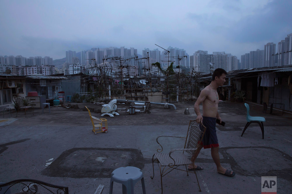"In this Saturday, May 6, 2017 photo, a resident walks outside his illegal rooftop hut located next to a public housing estate, in the background, in Hong Kong. In wealthy Hong Kong, there's a dark side to a housing boom, with hundreds of thousands of people forced to live in partitioned shoebox apartments, ""coffin homes"" and other ""inadequate housing. (AP Photo/Kin Cheung)"