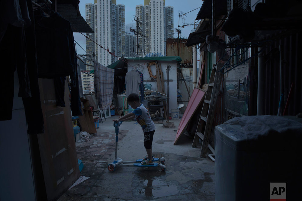 In this Thursday, April 20, 2017 photo, a five-year-old boy plays outside his tiny home which is made of concrete and corrugated metal on the terrace of a apartment block as he lives with his parents in an illegal rooftop hut located next to a public housing estate at the background in Hong Kong. (AP Photo/Kin Cheung)