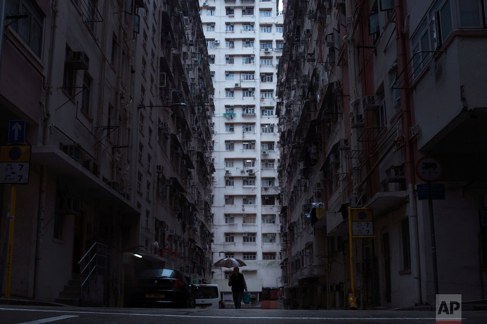 "In this Tuesday, April 25, 2017 photo, a man walks in front of a residential and commercial building, center, where the ""coffin home"" is located in Hong Kong. In wealthy Hong Kong, there's a dark side to a housing boom, with hundreds of thousands of people forced to live in partitioned shoebox apartments, ""coffin homes"" and other ""inadequate housing. (AP Photo/Kin Cheung)"