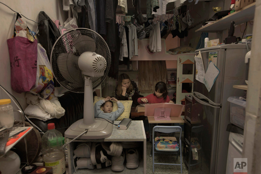 "In this Friday, March 17, 2017 photo, Li Suet-wen and her son, 6, and daughter, 8, live in a 120-square foot room crammed with a bunk bed, small couch, fridge, washing machine and small table in an aging walkup in Hong Kong as she pays HK$4,500 ($580) a month in rent and utilities. That's nearly half the HK$10,000 ($1,290) she earns at a bakery decorating cakes. They're among an estimated 200,000 people in the former British colony living in ""subdivided units."" That's 18 percent more than four years ago and includes 35,500 children 15 and under, government figures show. (AP Photo/Kin Cheung)"