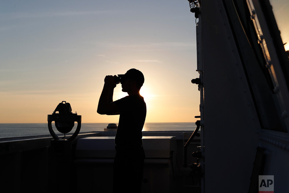In this Feb. 22, 2017 photo, a U.S. Coast Guard sailor scans the horizon with his binoculars just outside the bridge of the USCG cutter Stratton as it navigates the eastern Pacific Ocean near the coast of Central America. The Coast Guard set a record in 2016, seizing more than 240 tons of cocaine, but its victories seem doomed to be short-lived. That's because hundreds of miles to the south, in the jungles of Colombia, there's a bumper harvest taking place. And Colombia is virtually the only source of cocaine smuggled by sea in small vessels. (AP Photo/Dario Lopez-Mills)