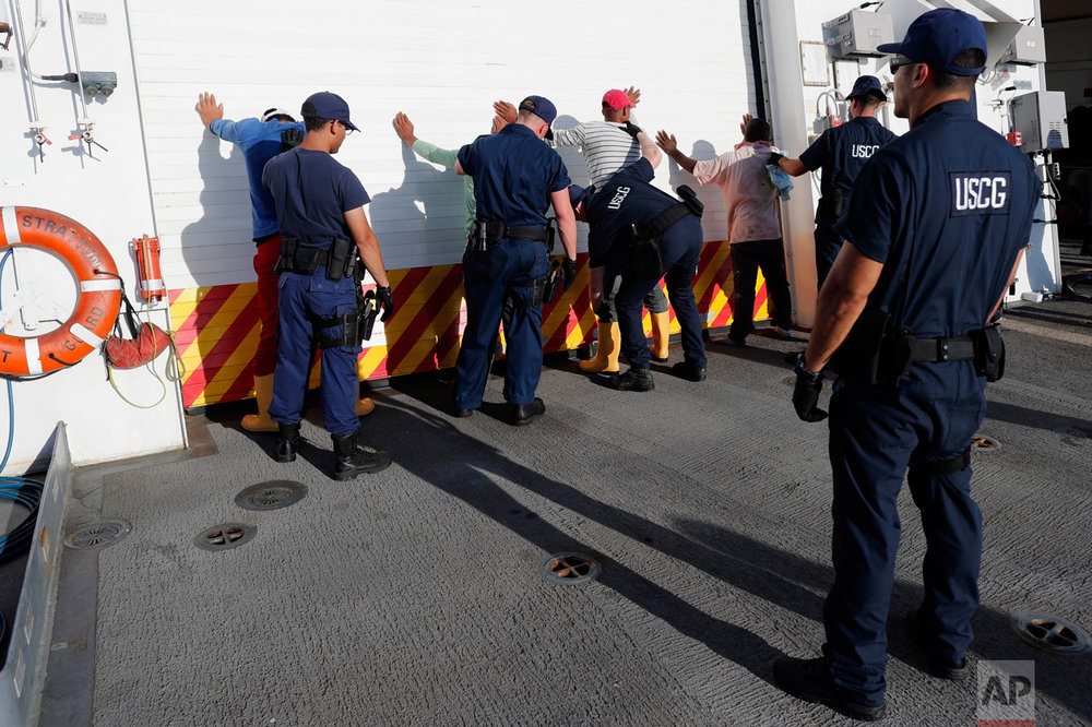 In this Thursday, Feb. 23, 2017 photo, four men who were caught transporting close to 700 kilos of cocaine in a small fishing boat are frisked in the flight deck of the U.S. Coast Guard cutter Stratton after they were detained the in Pacific Ocean, hundreds of miles south of the Guatemala-El Salvador border. (AP Photo/Dario Lopez-Mills)