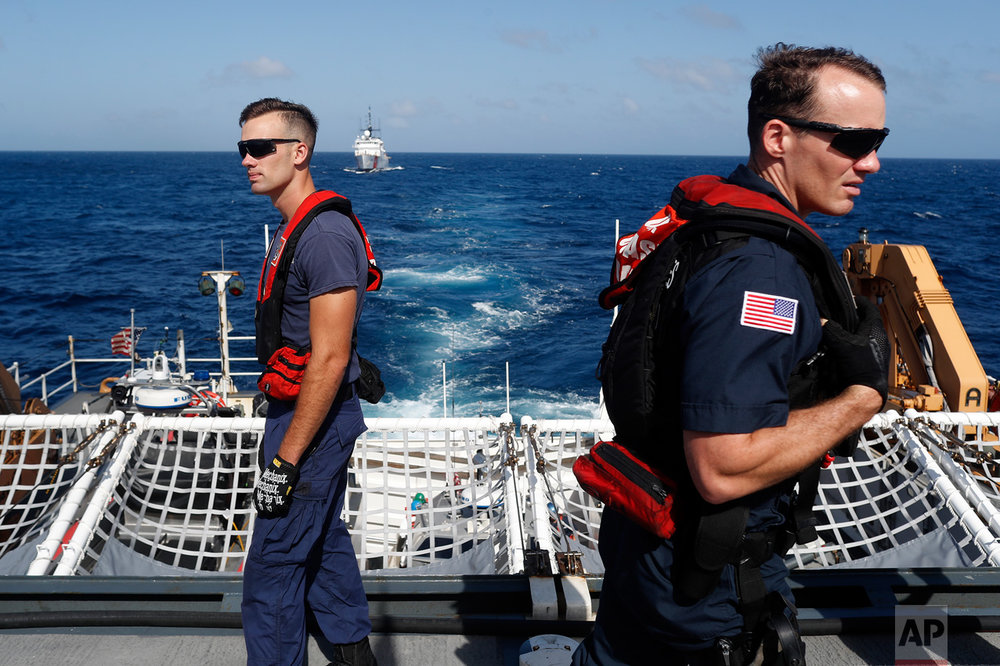 In this March 7, 2017 photo, two U.S. Coast Guardsmen watch as a suspects transfer operation is underway from the U.S. Coast Guard cutter Stratton to the U.S. Coast Guard cutter Mohawk, while sailing in the eastern Pacific Ocean. The Stratton is one of three to five Coast Guard cutters covering 6 million square miles, from the Caribbean and the Gulf of Mexico to the eastern Pacific Ocean searching for drug smugglers. (AP Photo/Dario Lopez-Mills)