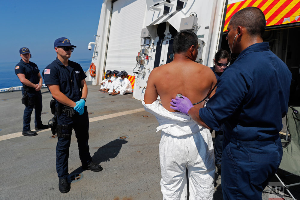 In this Feb. 26, 2017 photo, a U.S. Coast Guardsman performs a medical check on a drug trafficking suspect transferred from the USCG cutter Mohawk to the USCG cutter Stratton, in the eastern Pacific Ocean. Those taken into custody for smuggling are issued white hazmat suits, given health exams and then led into a converted helicopter hangar aboard the Stratton, where they are shackled to the floor and issued a wool blanket, toiletries and a cot or a foam mat. (AP Photo/Dario Lopez-Mills)