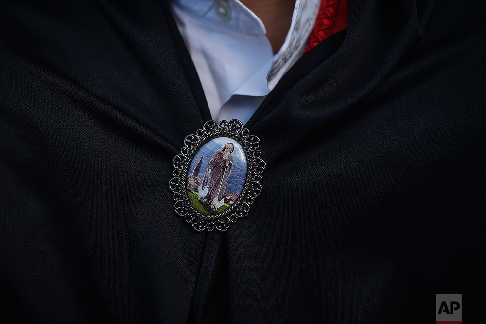 A medallion is seen on the neck of a dancer with the figure of Domingo de La Calzada Saint (1019-1109), who helped poor people and pilgrims, in Santo Domingo de La Calzada, northern Spain, Wednesday, May 10, 2017. (AP Photo/Alvaro Barrientos)