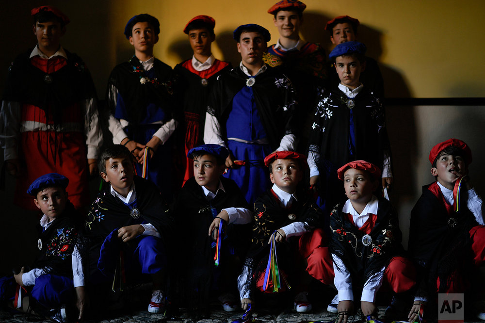 "Dancers who will accompany the ""Prioress Procession"" pose inside of the house Domingo de La Calzada Saint (1019-1109), a saint who helped poor people and pilgrimage, in Santo Domingo de La Calzada, northern Spain, Wednesday, May 10, 2017. Every year during spring season, ''Las Prioras'' (Prioresses) hold on their head a basket covered with white cloth and dress in black while they walk past along of this old village in honor of the saint. (AP Photo/Alvaro Barrientos)"