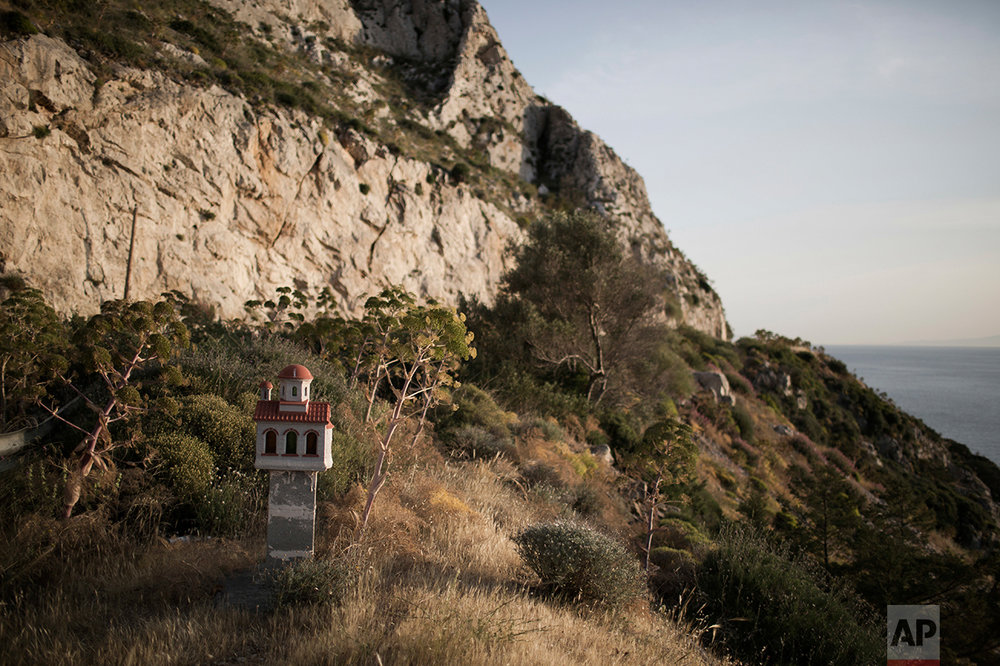 In this photo taken on Thursday, May 2, 2017, a roadside shrine stands near the sea at Cape Sounion, southeast of Athens. (AP Photo/Petros Giannakouris)