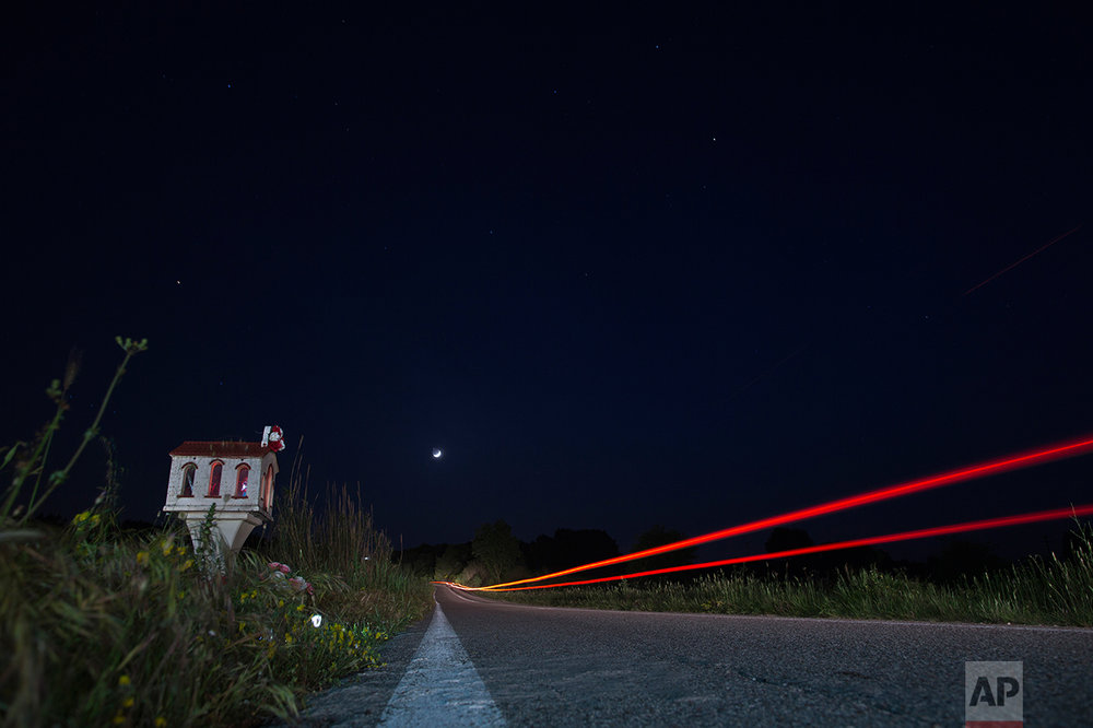 In this photo taken with a slow shutter speed on Friday, April 28, 2017, a car passes a roadside shrine near the village of Efyra, in the Peloponnese region of southern Greece. The shrine marks the spot where at dusk on Oct. 18, 2009, 19-year-old Nikos Staikopoulos lost control of his speeding car, crashed and died. (AP Photo/Petros Giannakouris)