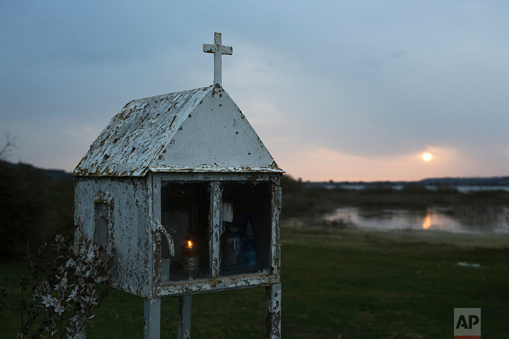 In this photo taken on Saturday, April 29, 2017, a candle is lit in a roadside shrine as the sun sets across a nearby lake of Pineia in the village of Souli, in the Peloponnese region of southern Greece. AP Photo/Petros Giannakouris)