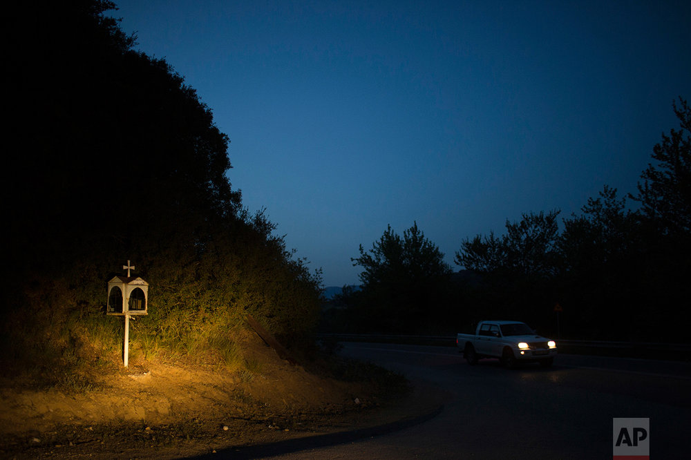 In this photo taken on Thursday, April 27, 2017, a car drives near an iron roadside shrine near the village of Avrami, in the Peloponnese region of southern Greece. (AP Photo/Petros Giannakouris)
