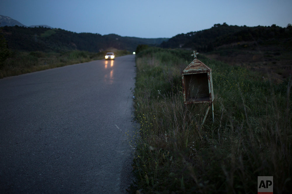 In this photo taken on Thursday, April 27, 2017, a car drives past an abandoned iron roadside shrine near the village of Kritharakia, in the Peloponnese region of southern Greece. (AP Photo/Petros Giannakouris)
