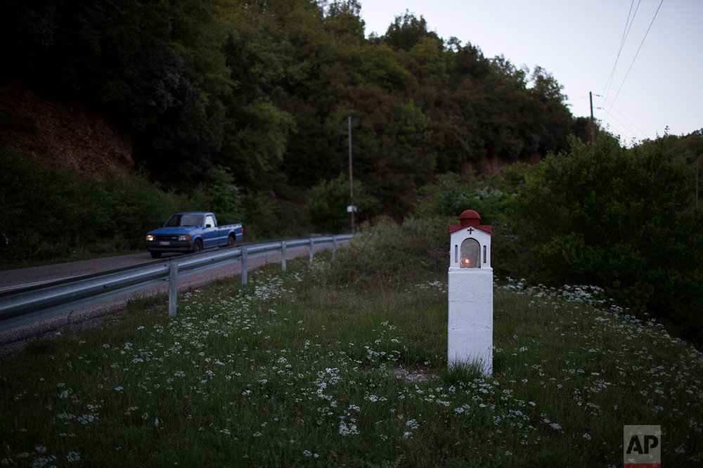 In this photo taken on Wednesday, April 26, 2017, a candle is lit in a roadside shrine near the village of Lalas, in the Peloponnese region of southern Greece. (AP Photo/Petros Giannakouris)