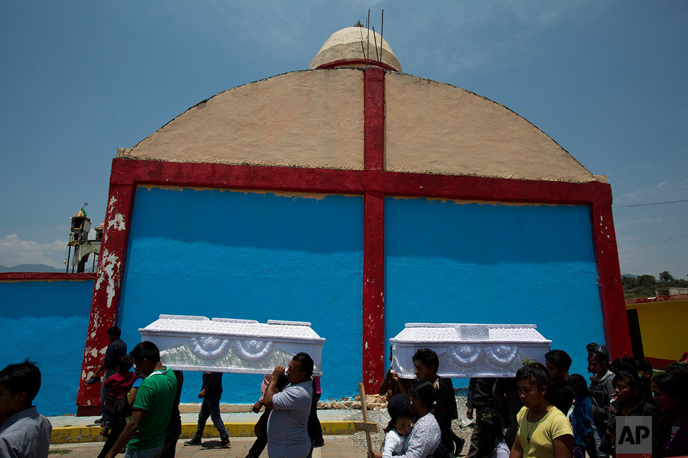 Mourners carry the coffins of young people killed in a fireworks explosion to the village church, in San Isidro, Puebla State, Wednesday, May 10, 2017. (AP Photo/Rebecca Blackwell)