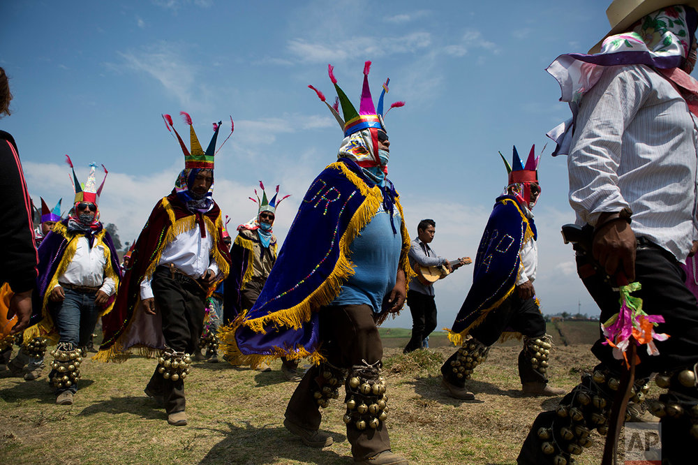 Traditional dancers accompany the coffins of 12 young people killed in a fireworks explosion, to a special burial plot on a hilltop overlooking the village of San Isidro, Puebla State, Wednesday, May 10, 2017. (AP Photo/Rebecca Blackwell)