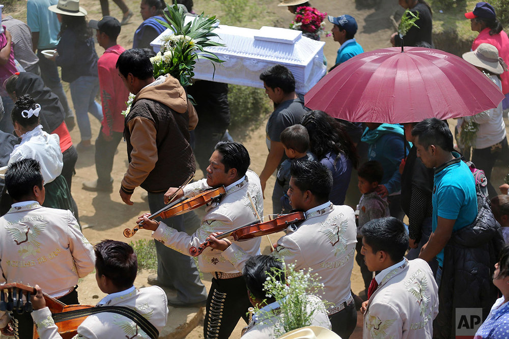 Mariachis play violins as a child-size coffin is carried during the funeral procession in the village of San Isidro, Puebla state, Wednesday May 10, 2017.  (AP Photo/Enric Marti)