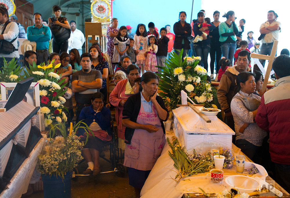 Family and friends hold a wake for 11 children killed in a fireworks explosion in the village of San Isidro, Puebla state, Mexico, Wednesday, May 10, 2017. (AP Photo/Rebecca Blackwell)