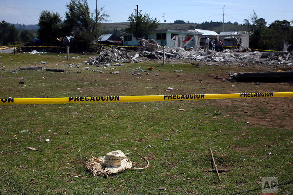 A straw hat and a cross made with two pieces of wood lie on the ground next to the site of a fireworks explosion that leveled a house and killed 14 people, including 11 children, in the village of San Isidro, Puebla state, Mexico, Wednesday, May 10, 2017. (AP Photo/Enric Marti)