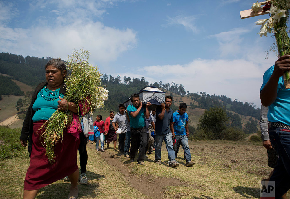 People accompany the coffin of one of the 12 people killed in a fireworks explosion, to a special burial plot atop a hill overlooking the village of San Isidro, Puebla State, Wednesday, May 10, 2017. (AP Photo/Rebecca Blackwell)