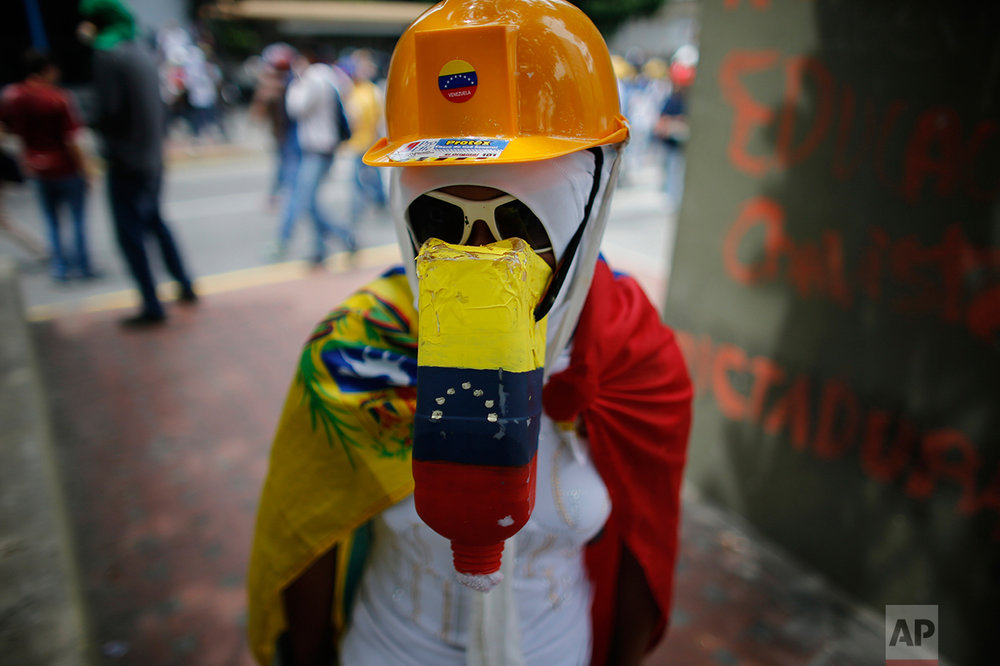 In this May 8, 2017 photo, a woman protects herself with a helmet, sunglasses, clothing and a plastic bottle stuffed with cotton balls during an anti-government protest in Caracas, Venezuela. In a country where finding even a Tylenol can be a weeks-long ordeal, protesters are employing every scrap of material they can to protect themselves while confronting police and national guardsmen who fire tear gas and rubber bullets to disperse marchers. (AP Photo/Ariana Cubillos)
