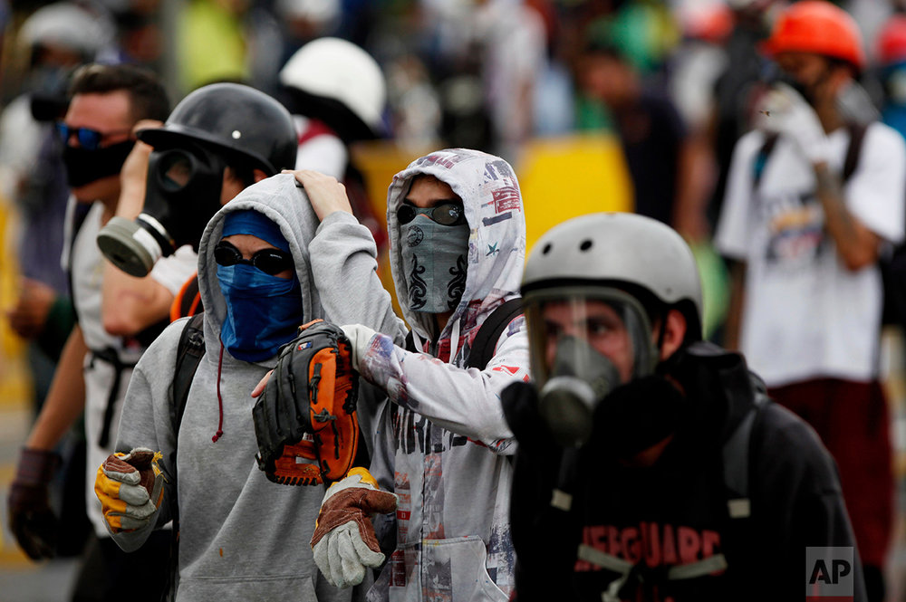 In this May 8, 2017 photo, a demonstrator wears a baseball glove to catch tear gas canisters launched by Bolivarian National Guards during an anti-government protest in Caracas, Venezuela. Some of the canisters land close to protesters, and the opposition contends several demonstrators have died after being struck, though official causes of death have not been released. (AP Photo/Fernando Llano)