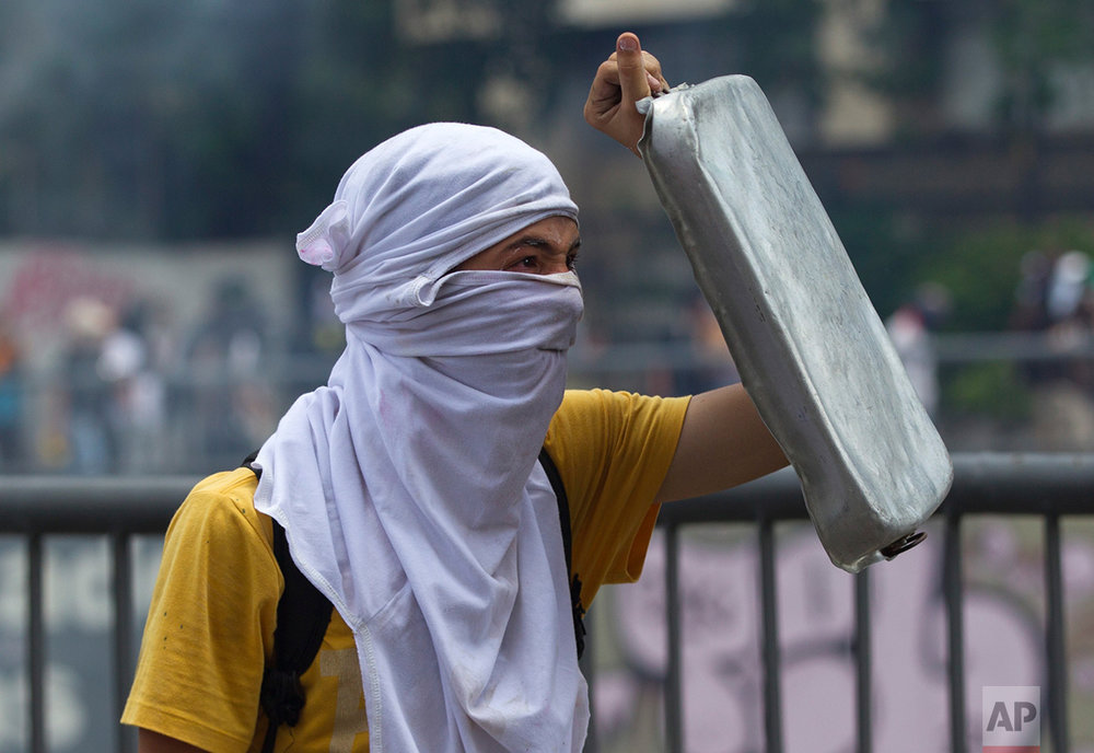 In this April 8, 2017 photo, an anti-government demonstrator shields himself with a cooking pan during clashes with Bolivarian National Guards in Caracas, Venezuela. At least 38 people have been killed and hundreds injured in protests that erupted after the Supreme Court issued a ruling March 29 nullifying the opposition-controlled National Assembly, a decision it later reversed amid a storm of international criticism and outrage among Venezuelans. (AP Photo/Ariana Cubillos)