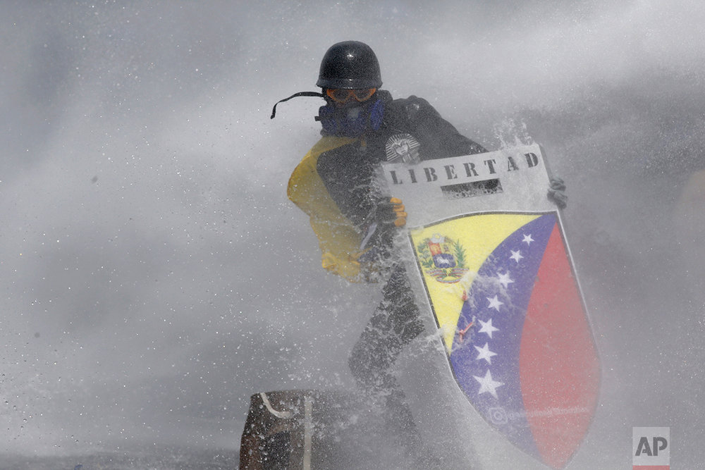 "In this May 10, 2017 photo, amid a cloud of tear gas, an anti-government protester wearing a helmet, googles, gas mask and gloves holds a shield with the Spanish word ""Freedom,"" to protect himself from a water cannon fired by security forces in Caracas, Venezuela. The government's response to the demonstrations has drawn international condemnation, with U.S. Secretary of State Rex Tillerson expressing concern in April that Maduro is ""not allowing the opposition to have their voices heard."" (AP Photo/Ariana Cubillos)"
