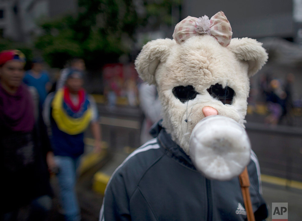 In this April 13, 2017 photo, an anti-government demonstrator wears a homemade teddy bear gas mask during a march in Caracas, Venezuela. Drawing rail-thin teenagers, elderly grandmothers and all ages in between, Venezuela's protests have taken on an almost ritual-like progression: Demonstrators begin marching toward their chosen destination and are blocked by police or national guardsmen in armored trucks launching plumes of tear gas. (AP Photo/Ariana Cubillos)