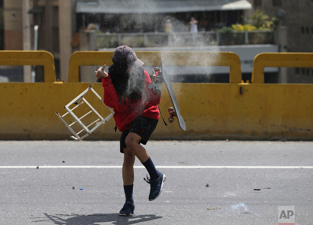 In this April 6, 2017 photo, an anti-government demonstrator deflects a tear gas canister with his skateboard during clashes with Bolivarian National Guards in Caracas, Venezuela. President Nicolas Maduro blames the opposition for the violence, claiming its leaders are instigating the unrest and working with gangs to remove him from power. At least two law enforcement officers have been killed, while 36 civilians have died during the protests. (AP Photo/Fernando Llano)