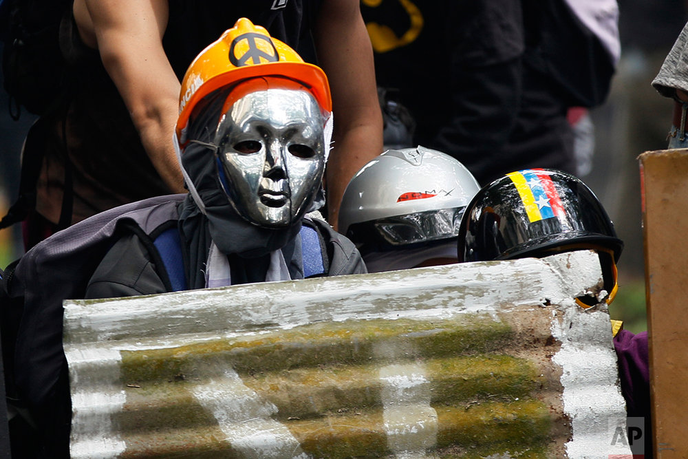 In this May 1, 2017 photo, a masked and helmeted anti-government demonstrator takes cover behind a sheet metal shield during clashes with security forces on May Day in Caracas, Venezuela. Behind the front line of security forces stands another group protected with gas masks firing tear gas and rubber bullets to push protesters back. Other officers on motorcycles emerge from the periphery to make arrests. (AP Photo/Ariana Cubillos)