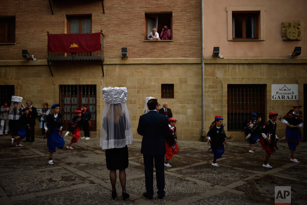 Participants of ''Prioresses Procession'', take part in the ceremony in honor of Domingo de La Calzada Saint (1019-1109), who helped poor people and pilgrims, in Santo Domingo de La Calzada, northern Spain, on Wednesday, May 10, 2017. Every year during the spring, ''Las Prioras'' (Prioresses) don a basket covered with white cloth and dress in black while they walk through the old village in honor of the saint. (AP Photo/Alvaro Barrientos)