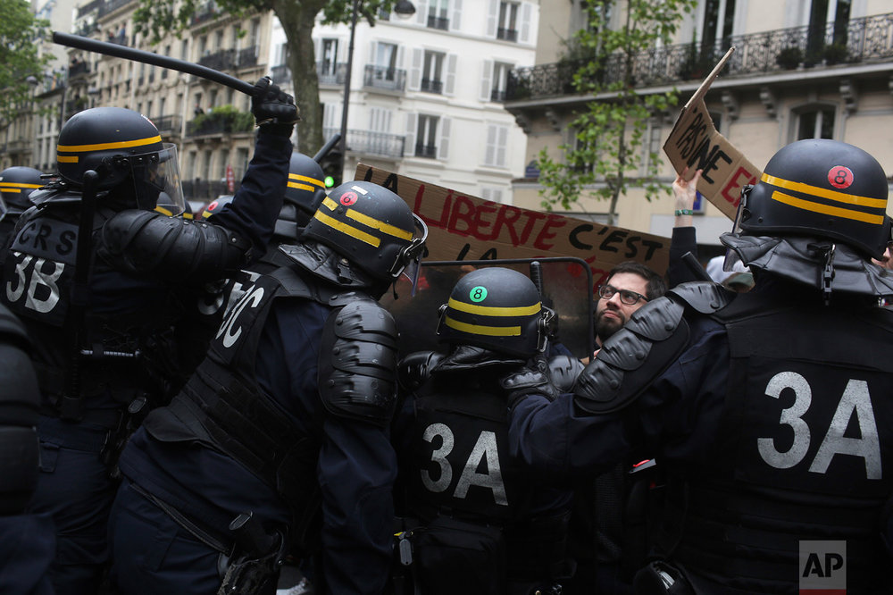 "Police clash with protesters during a demonstration called by labor unions the day after the French presidential election, in Paris on Monday, May 8, 2017. Former civil servant and investment banker French President-elect Emmanuel Macron and his fledgling political movement La Republique En Marche (Republic On the Move), are preparing for government after defeating far-right National Front leader Marine Le Pen in Sunday's presidential runoff vote. Placard at center reads ""Freedom."" (AP Photo/Thibault Camus)"