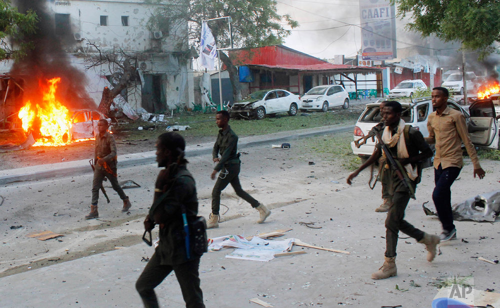 Security troops walk past burning cars after a fatal car bomb attack on a restaurant in Mogadishu, Somalia, on Monday, May, 8, 2017. Al-Shabab, Somalia's homegrown Islamic extremist rebels who are linked to al-Qaida, have claimed responsibility for the blast. Despite being ousted from most cities and towns, al-Shabab continue to carry out deadly attacks in Mogadishu and across large parts of Somalia. (AP Photo/Farah Abdi Warsameh)