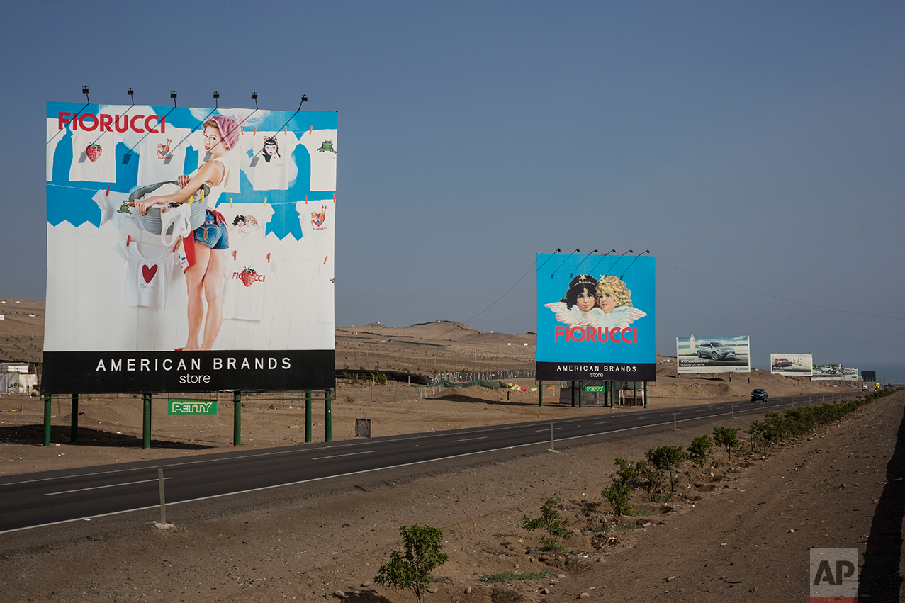 In this May 5, 2017 photo, billboards advertising a clothing store and vehicles line the Pan-American Highway on the south side of Lima, Peru. As the cars zoom by on their way to private beaches, people labor in the dusty terrain earning not enough to be able to afford any of the goods advertised on the billboards. (AP Photo/Rodrigo Abd)