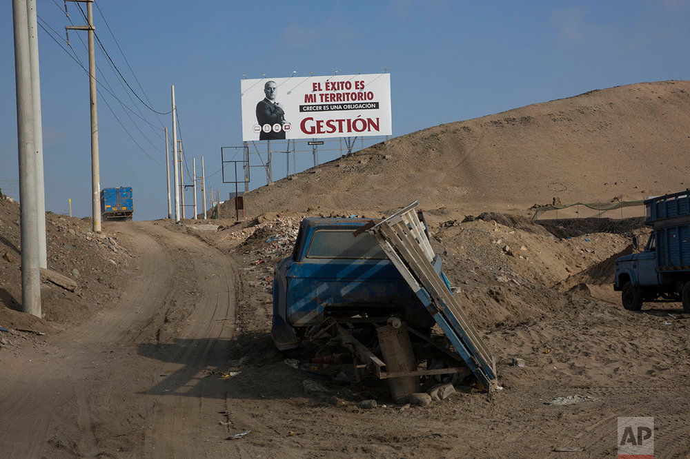 "In this May 5, 2017 photo, a billboard advertising the economic magazine ""Gestion"" reads in Spanish: ""Success is my territory. Growing is an obligation,"" along the Pan American Highway where a vehicle sits abandoned, on the south side of Lima, Peru, Friday, May 5, 2017. Trash is scattered around the area where people live in homes without potable water and adequate public services, menaced by local gangs that invade and traffic in properties. (AP Photo/Rodrigo Abd)"