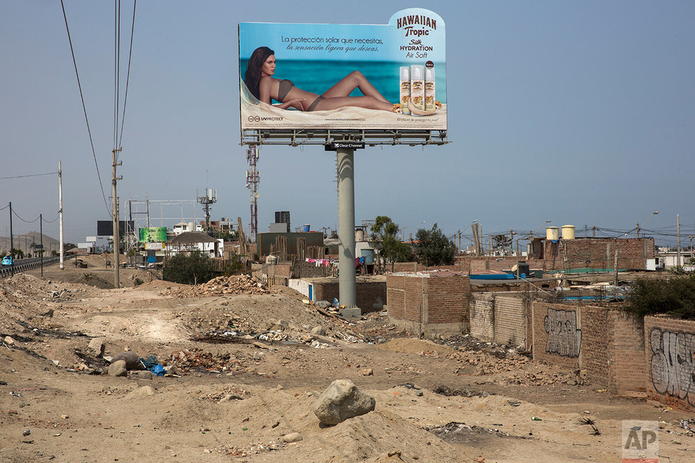 "In this May 5, 2017 photo, a billboard advertising sunscreen with a woman sunbathing on a beach stands high above a poor neighborhood of cinderblock shack homes along the Pan American Highway on the south side of Lima, Peru, Friday, May 5, 2017. Wilfredo Ardito, a law professor from the Pontifical Catholic University of Peru who has studied the country's racism, says that advertising in the Andean nation underscores its great inequalities, showing ""the ideal world of happiness in which everyone is white and all of those who are not white have disappeared."" (AP Photo/Rodrigo Abd)"