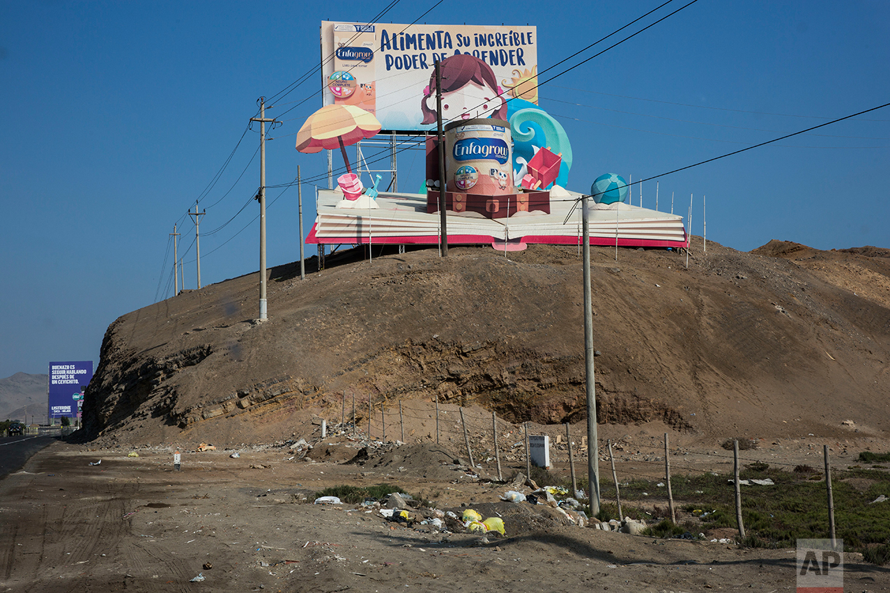"In this May 5, 2017 photo, a giant billboard advertising powdered milk reads in Spanish ""Feed your incredible power to learn"" as it stands on a hill along the Pan American Highway on the south side of Lima, Peru. As the cars zoom by on their way to private beaches, people labor in the dusty terrain earning wages so lo that they would hardly be able to purchase any of the goods advertised in the billboards. (AP Photo/Rodrigo Abd)"
