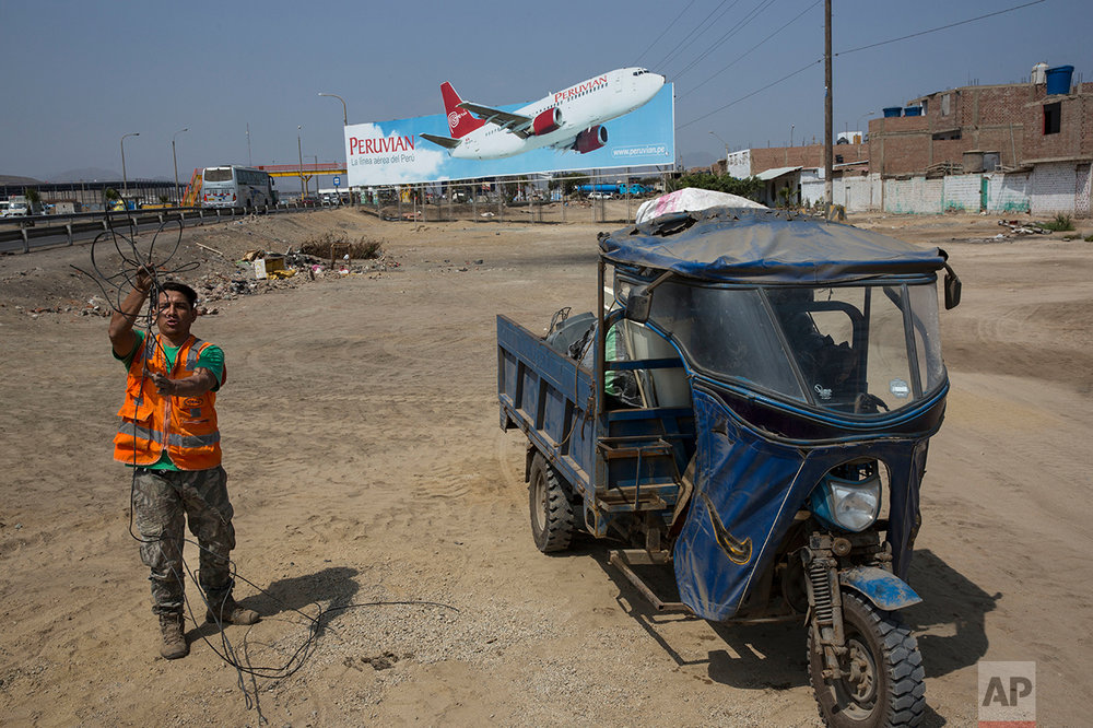 In this May 5, 2017 photo, a man collects cables for resale, along with other recyclable objects, along the Pan American Highway where a billboard advertises a local airline on the south side of Lima, Peru. Below the billboards are cannibalized cars, piles of used brick and white crosses marking the places where people died along the highway. (AP Photo/Rodrigo Abd)
