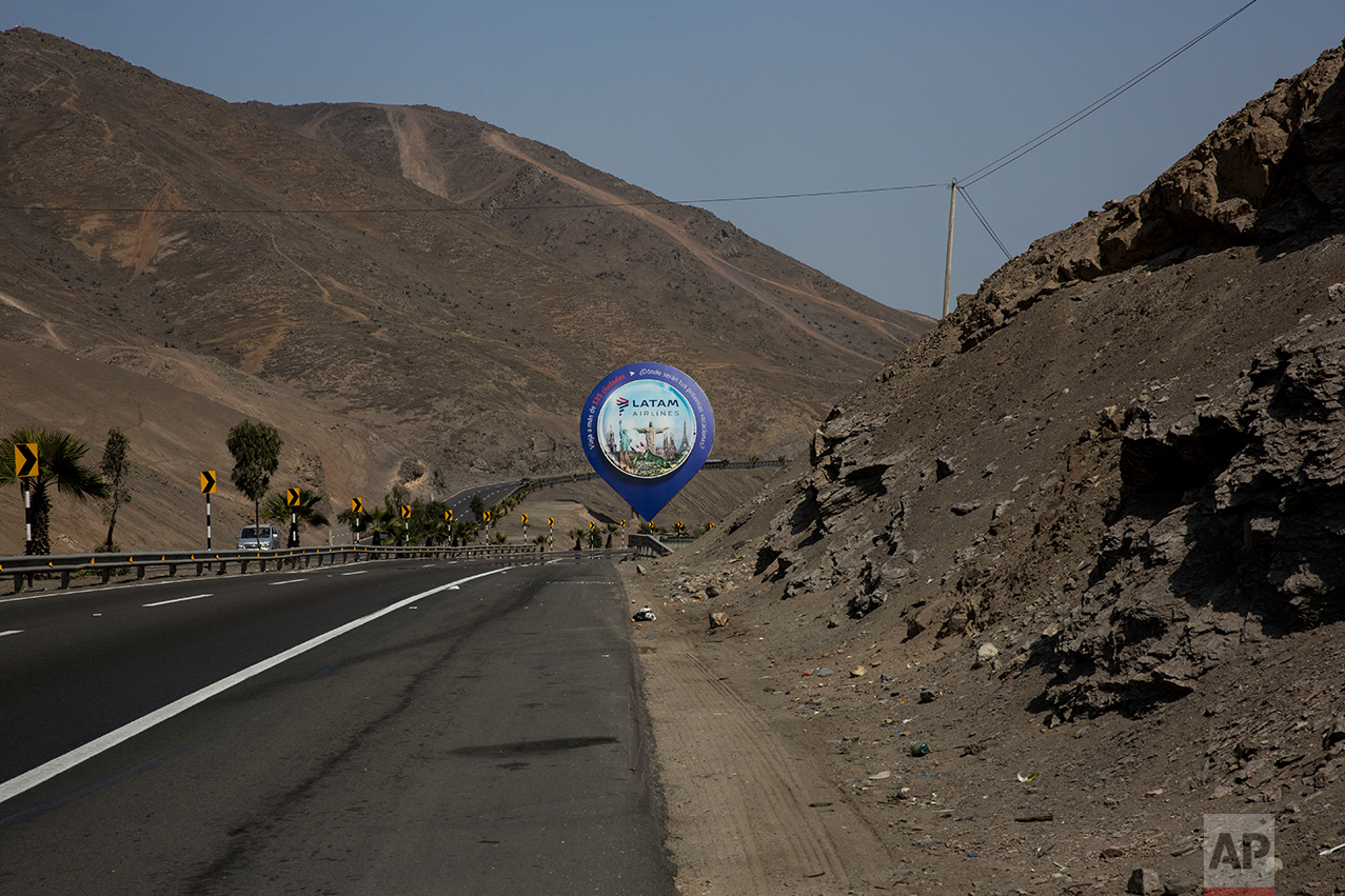 In this May 5, 2017 photo, a billboard advertising an airline stands along the Pan American Highway on the south side of Lima, Peru. The billboards advertise products the people living in this area are unlikely to be able to buy or afford. (AP Photo/Rodrigo Abd)