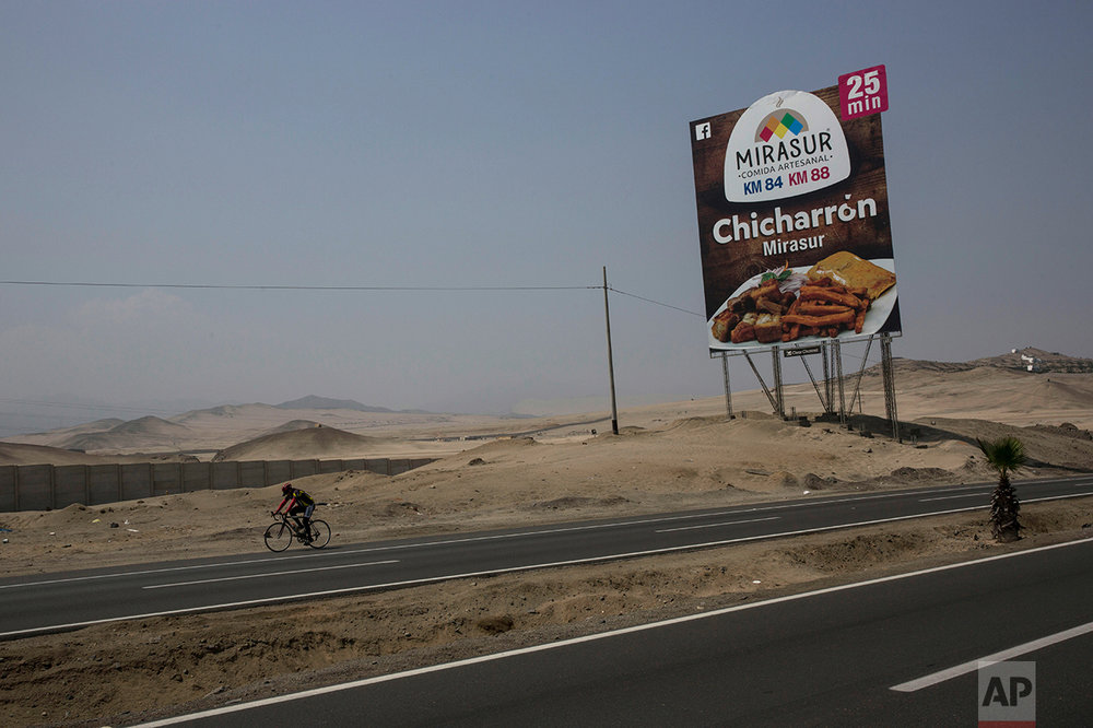 In this May 5, 2017 photo, a cyclist passes a billboard advertising a restaurant along the Pan American Highway on the south side of Lima, Peru. Below the billboards are cannibalized cars, piles of used brick and white crosses marking the places where people died along the highway. (AP Photo/Rodrigo Abd)
