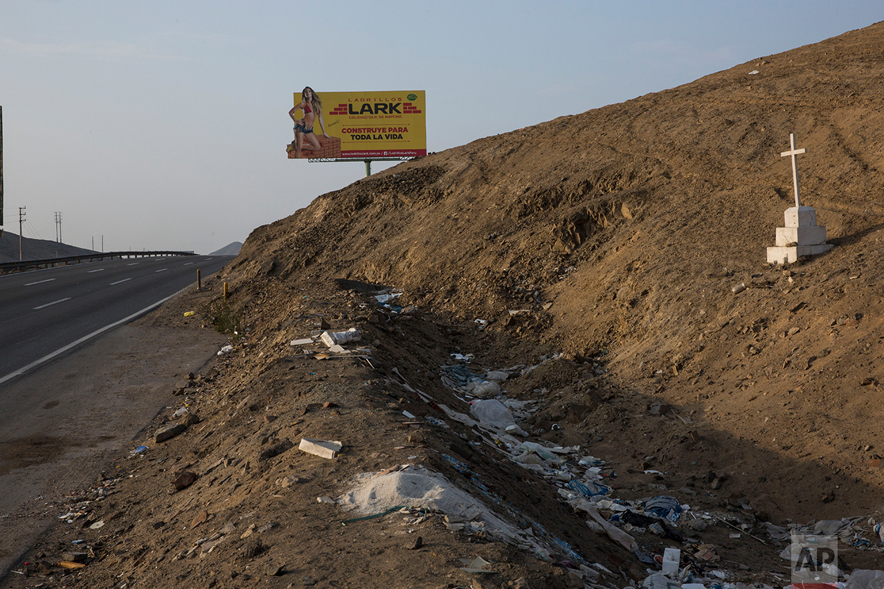 In this May 5, 2017 photo, a billboard advertising construction materials stands along the Pan American Highway where a cross marks the spot where someone was killed, on the south side of Lima, Peru. Below the billboards are cannibalized cars, piles of used brick and white crosses marking the places where people died along the highway. (AP Photo/Rodrigo Abd)