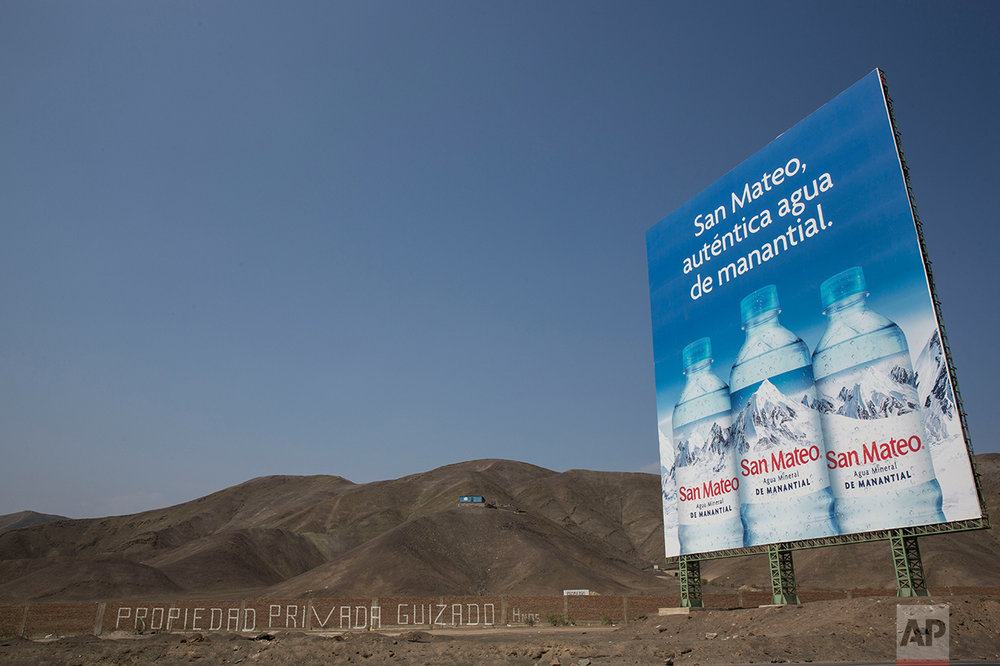 In this May 5, 2017 photo, a billboard advertising spring water stands along the Pan American Highway on the south side of Lima, Peru. Trash is scattered around the area where people live in homes without potable water and adequate public services, menaced by local gangs that invade and traffic in properties. (AP Photo/Rodrigo Abd)