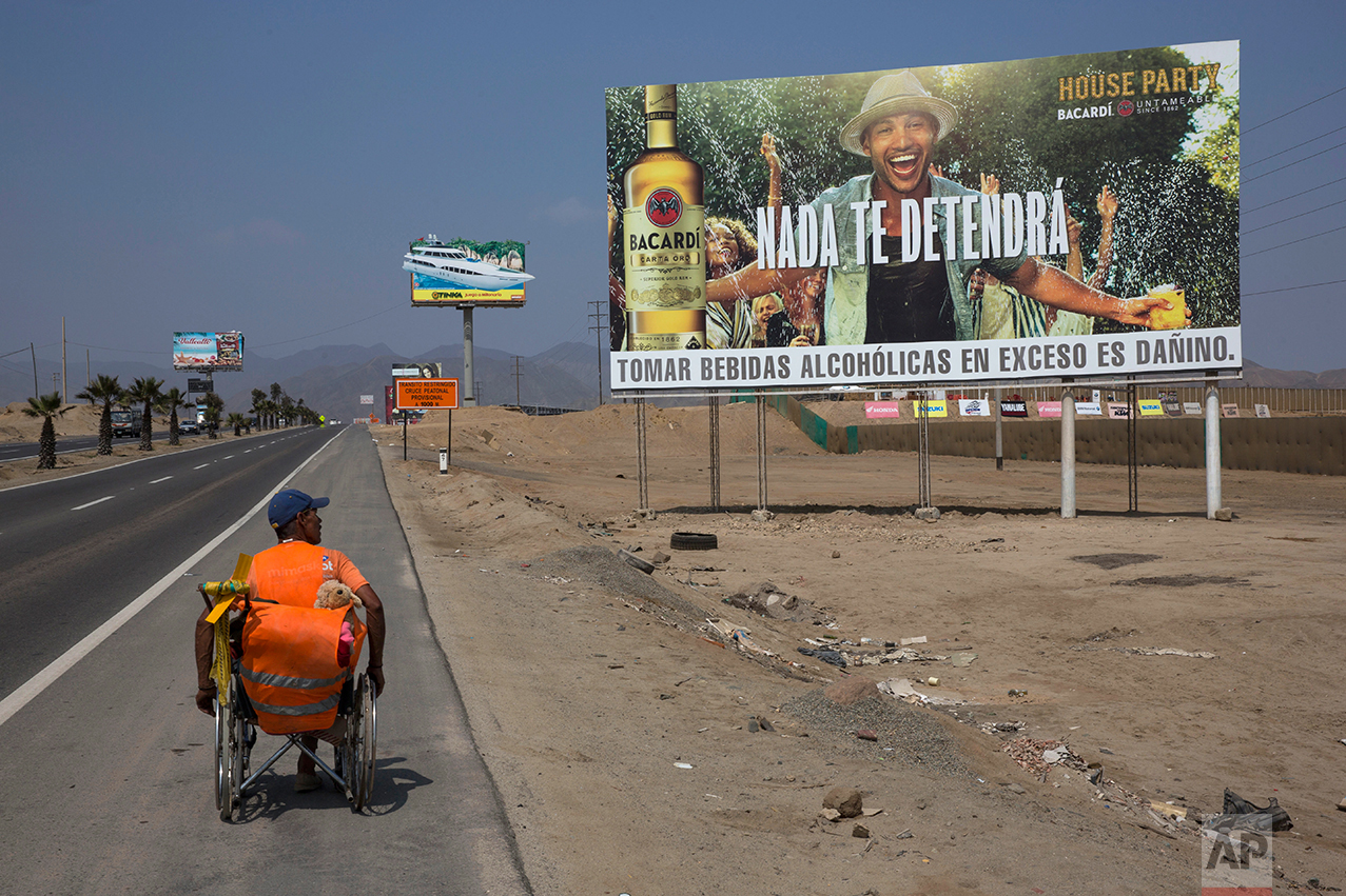 "In this May 5, 2017 photo, Jose Suarez, from Cucuta, Colombia, moves his wheelchair, decorated with a stuffed animal, along the Pan American Highway lined with billboards advertising rum, lottery and mixed nuts, on the south side of Lima, Peru. Suarez, 58, said he's on a mission to reach Brazil in his wheelchair, after leaving Cucuta in January. The billboard reads in Spanish ""Nothing will stop you."" (AP Photo/Rodrigo Abd)"