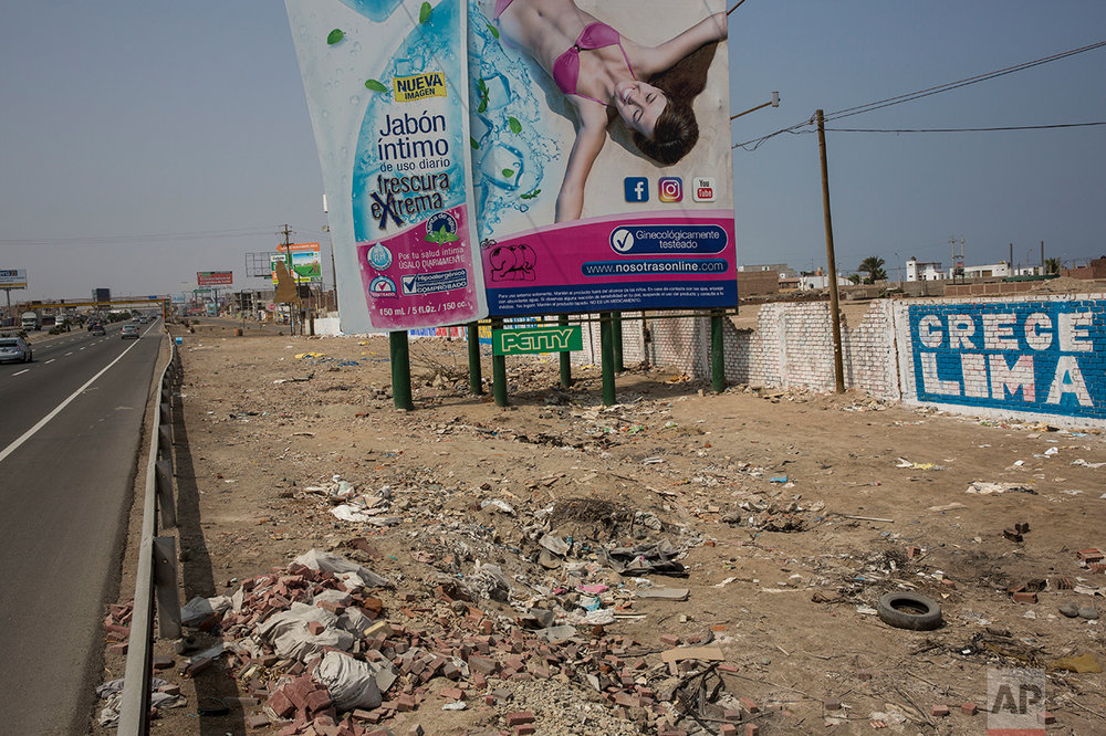 "In this May 5, 2017 photo, a billboard advertising a soap brand stands among trash strewn along the Pan American Highway on the south side of Lima, Peru. Wilfredo Ardito, a law professor from the Pontifical Catholic University of Peru who has studied the country's racism, says that advertising in the Andean nation underscores its great inequalities, showing ""the ideal world of happiness in which everyone is white and all of those who are not white have disappeared."" (AP Photo/Rodrigo Abd)"