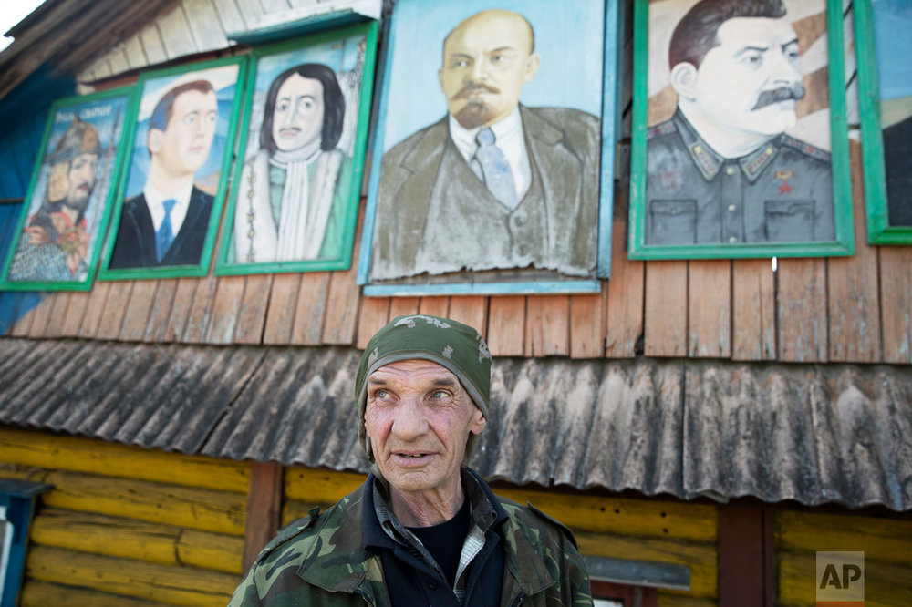 In this photo taken on Wednesday, May 3, 2017, Mikhail Korhunov stands in front of his paintings, portraits of (from left): Russian Prime Minister Dmitry Medvedev, Russian czar Peter the Great, Soviet founder Vladimir Lenin and Soviet leader Josef Stalin, at the top of Korhunov's house in the village of Severnaya Griva, about 130 kilometers (80 miles) east of Moscow, Russia. (AP Photo/Pavel Golovkin)