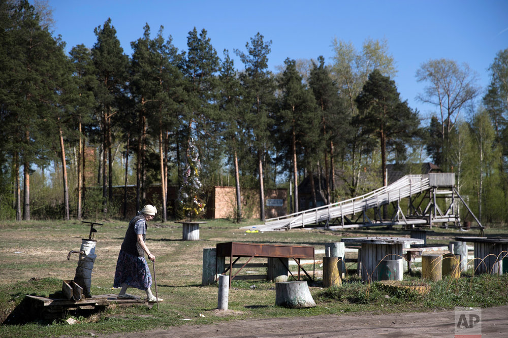 In this photo taken on Wednesday, May 3, 2017, an elderly woman walks past a wooden slope, which was built by Mikhail Korhunov, in the village of Severnaya Griva, about 130 kilometers (80 miles) east of Moscow, Russia. (AP Photo/Pavel Golovkin)