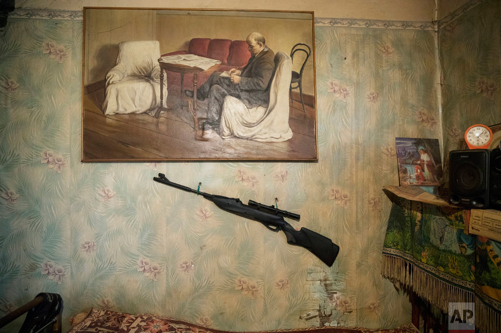 In this photo taken on Wednesday, May 3, 2017, a hunting rifle and a portrait of Soviet founder Vladimir Lenin are placed on a wall of Korhunov's house in the village of Severnaya Griva, about 130 kilometers (80 miles) east of Moscow, Russia. (AP Photo/Pavel Golovkin)